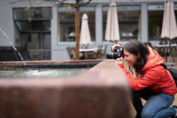 Kursteilnehmerin fotografiert Brunnen